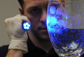 Special Agent Adam Deem shines light on a glass to reveal fingerprints (U.S. Air Force photo/Airman 1st Class Micaiah Anthony)